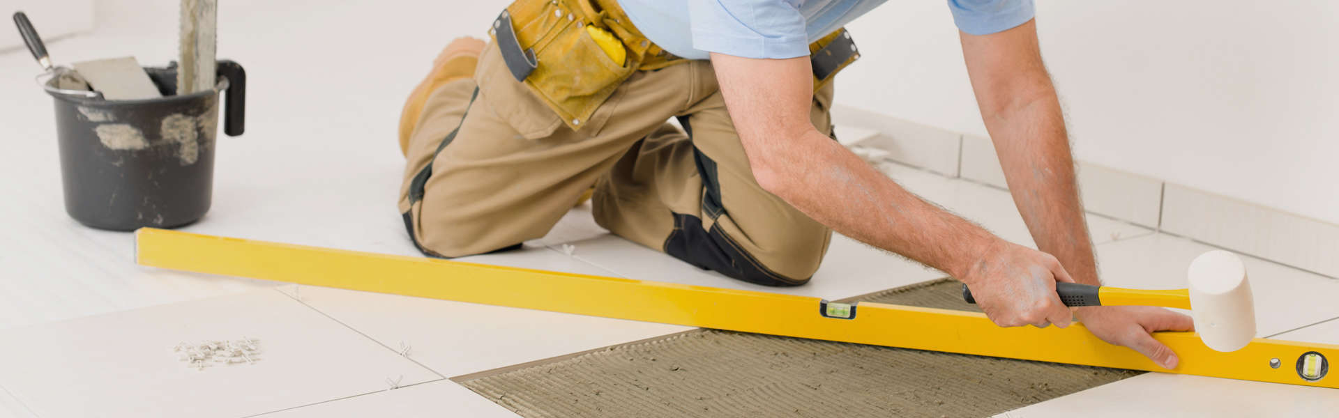 Image of man laying floor tiles by Carpet Cleaning Cheltenham